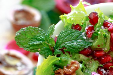 Close up of curly endive salad with pomegranate, nuts...