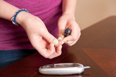 Girl testing her blood glucose level