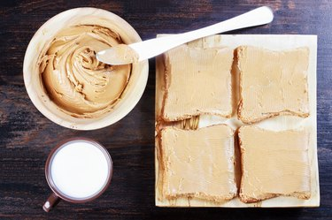 Sandwiches with peanut butter on wooden plate, peanut butter in