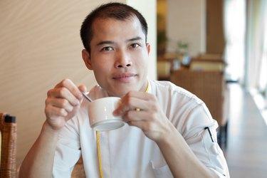 Chinese chef wearing uniform enjoying coffee break in restaurant cafe