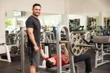 Portrait of a handsome young Hispanic man spotting his friend on the bench press while working out at a gym
