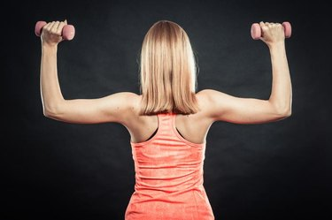Bodybuilding. Strong fit woman exercising with dumbbells. Muscular blonde girl lifting weights back view studio shot on black background