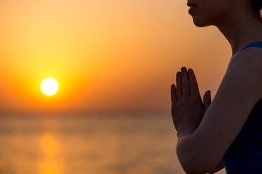 Profile of serene young woman relaxing on the beach, meditating with hands in Namaste gesture at sunset or sunrise, close up