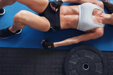 Top view cropped shot of muscular female lying on exercise mat with a heavy weight plate on floor.