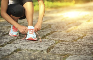 young fitness woman tying shoelaces on trail