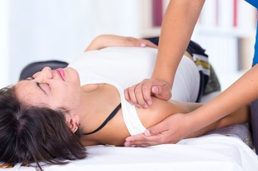 woman in pain lying while getting a shoulder massage concept