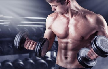Close up of a muscular young man lifting weights in gym