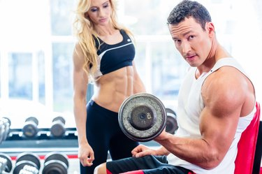 Couple in fitness gym with dumbbells lifting weight