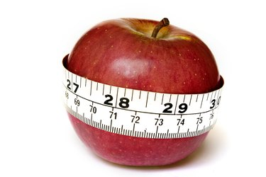 A stock photograph of an apple with a measuring tape around it.