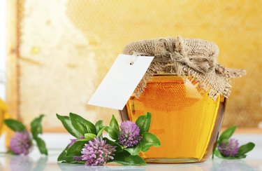 sweet honey in glass jars with flowers