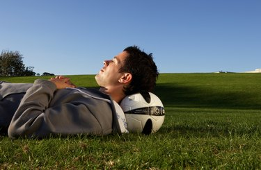 Young man lying in field with football under head, profile