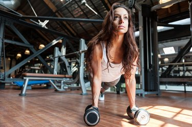 Young woman at gym doing pushups on dumbbells