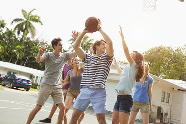 Group Of Young Friends Playing Basketball Match