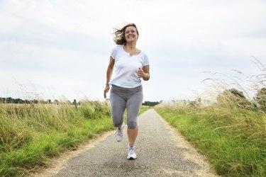active mature woman jogging outdoors