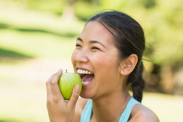 Cheerful young woman eating apple in park