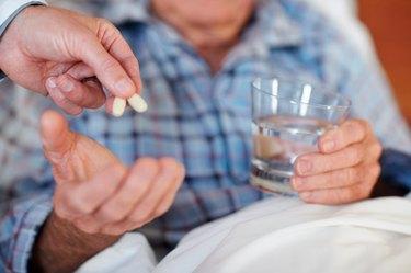Closeup of a senior man being given a life saving pill