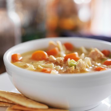 chicken noodle soup with crackers close up