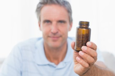 Man showing bottle of pills to camera