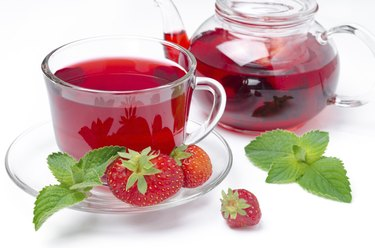 kettle and cup of red tea with strawberries, mint