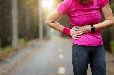 Side stitch - woman runner side cramps. Marathon.