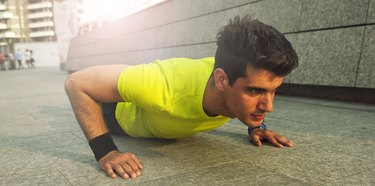 Picture of young handsome athletic man doing pushups