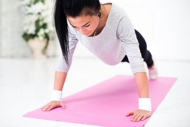 Young latin woman warming up and doing push ups at home fitness healthy lifestyle and diet concept