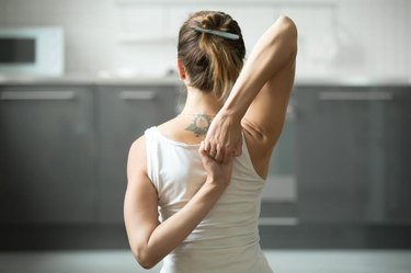 Close up of female hands behind the back, woman practicing yoga, sitting in Cow Face exercise, Gomukasana pose, working out, wearing white sportswear, indoor, home interior background