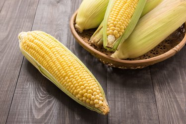 Fresh organic yellow sweet corn on wooden table