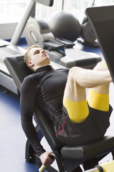 Young man using leg press machine