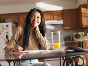 happy teen girl doing home work