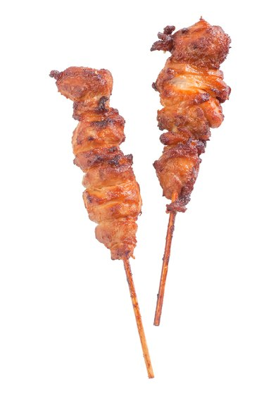 Chicken satay – grilled chicken skewers isolated on white background
