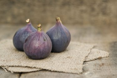 Fresh figs with hessian napkins on wooden background