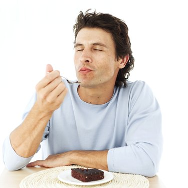 portrait of a man savoring a brownie with his eyes closed
