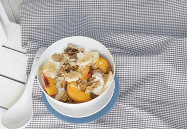 with bowl of cereal and fruit on orange tablecloth