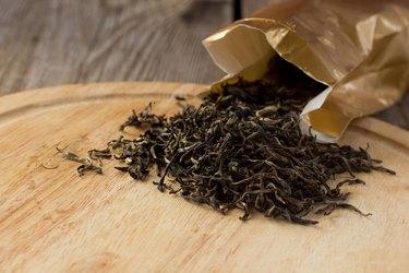 Dry white tea leaves on wooden plate