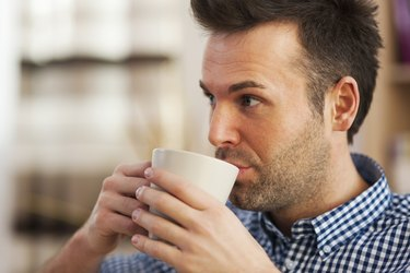 Close up man drinking coffee in home