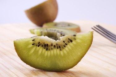 A studio shot of several slice of kiwifruit