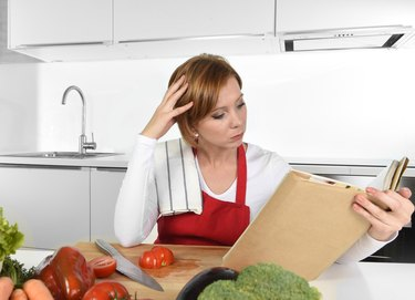 young beautiful home cook woman in kitchen reading cookbook