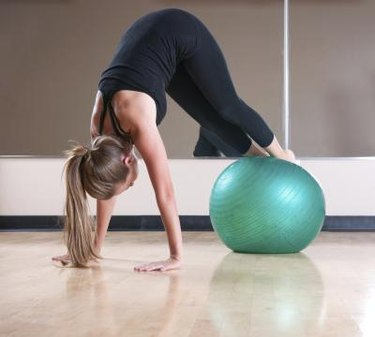 Woman in black workout cloths performs ab exercises in a fitness studio using a large exercise green ball.