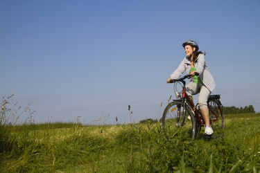 Young woman cycling through field
