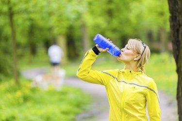 Female runner drinking water