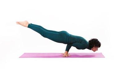 woman practice yoga peacock pose studio shot