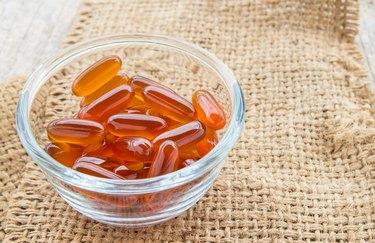 Fish oil capsules in glass bowl on burlap sack