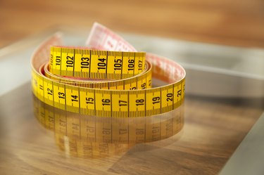 Measuring tape on weight scale.