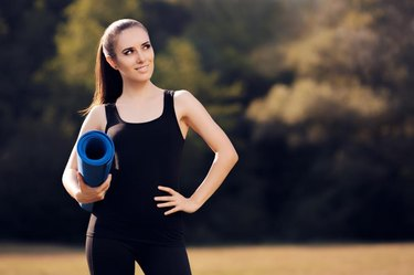 Fit woman with exercise accessory in summertime landscape