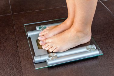 Closeup of woman feet standing on bathroom scale