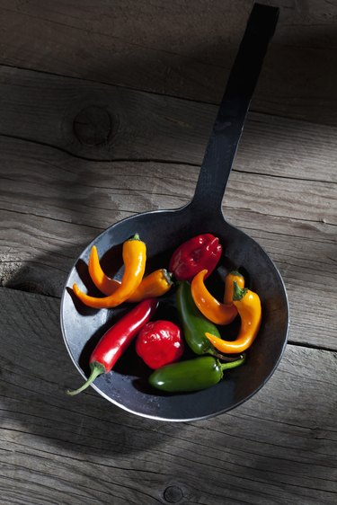 Habanero, Jalalpeno and chili peppers in frying pan on wood