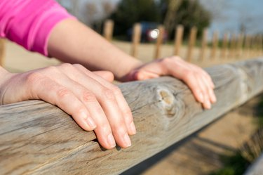 hands over a wooden fence