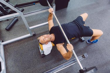 Handsome man doing exercises with barbell on a bench press training in a fitness center