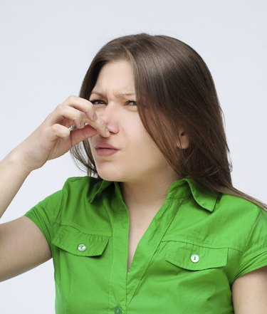 Portrait of disgusted young woman pinches her nose